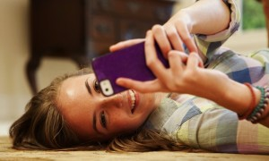 Teenage girl lying on floor with cell phone